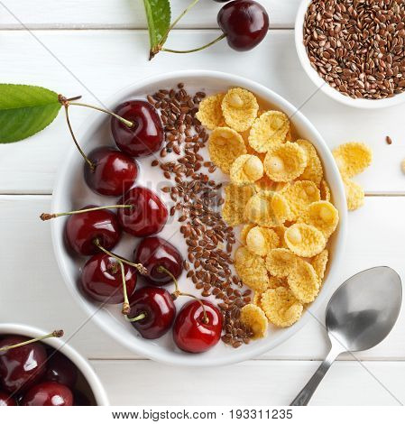 Healthy Breakfast With Corn Flakes, Greek Yogurt, Sweet Cherry And Flax Seeds In White Table.