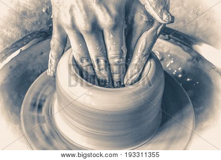 Old vinage style photo. Girl sculpts in clay pot closeup.