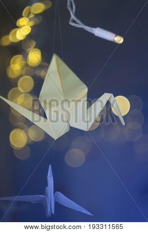 Paper yellow crane origami on a dark Christmas background garland.
