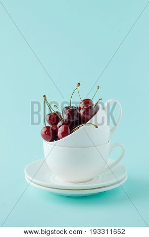 Stack Of Two White Teacup With Sweet Cherry On Cyan Background.