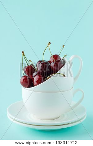 Stack Of Two White Teacup With Sweet Ripe Cherry On Pastel Cyan Background.
