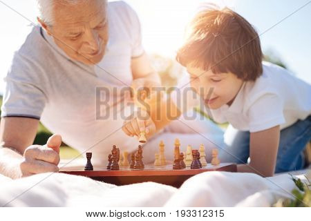 Learning something new. Elderly productive smart gentleman teaching his grandson about the rules and strategy of an intellectual game while enjoying picnic with him