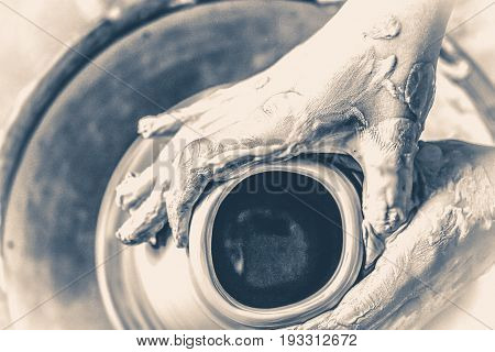 Photo in old vintage style. Girl sculpts in clay pot closeup. Modeling clay close-up. Caucasian man making vessel daytime of white clay in fast moving circle.