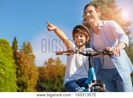 Dad, look. Enthusiastic bright lively kid spending an active day with his parent and suggesting they taking a ride somewhere