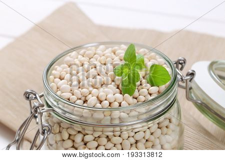 jar of raw white beans on beige place mat - close up