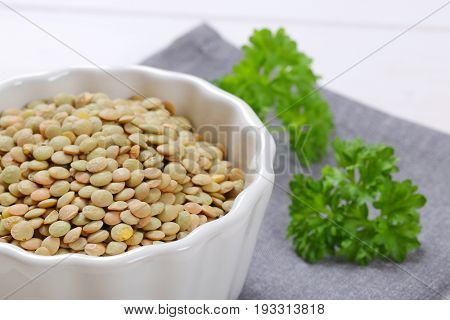 bowl of peeled brown lentils on grey place mat - close up