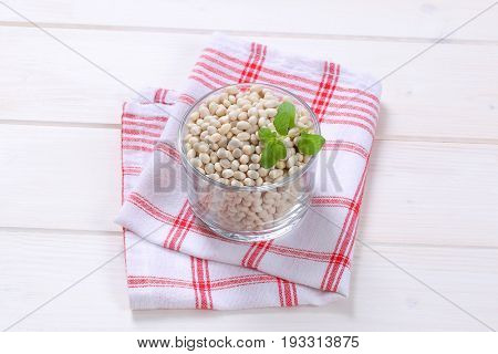 glass of raw white beans on checkered dishtowel