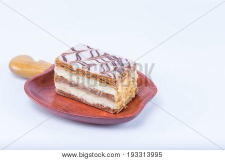 Mille-feuille Napoleon French Pastry On A Cashew Fruit Format Massaranduba Wood Dish Isolated On Whi