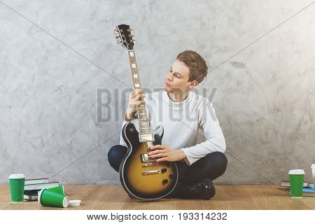 Handsome young man playing the guitar while sitting on wooden floor with multiple coffee cups. Rehearsal concept