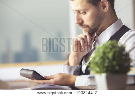 Portrait of attractive caucasian male accountant using calculator while sitting at office desk with devices and other items
