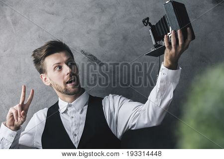Businessman showing peace gesture and taking selfie with a retro camera