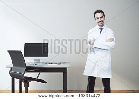 Happy male doctor with folded amrs standing in concrete office interior with blank computer on desktop. Mock up 3D Rendering