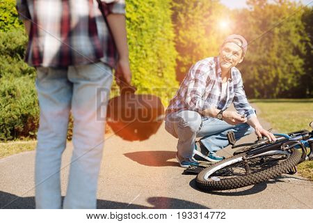 Teaching handy things. Devoted intelligent nice parent giving his child a lesson on how fixing his bike if it failing working