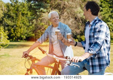 Lovely meeting. Easy going positive handsome man and his son taking some drinks to go while enjoying ride in the park and chatting pleasantly