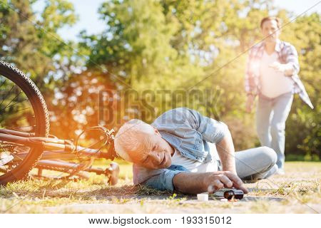 Big trouble. Anxious aged gentleman in pain lying on the ground and trying reaching the bottle of pills near him while falling from the bicycle due to collapse