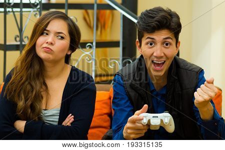 Happy young man playing video games on the couch while girlfriend is bored, concept about home entertainment, video games.