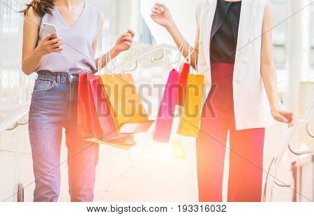 two young women hand holding smart phone and shopping bag sale consumerism and people concept.