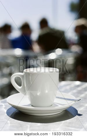 closeup of a cup of coffee on the table of the terrace of a cafe outdoors