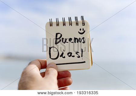 closeup of a young caucasian man outdoors showing a spiral notepad with the text buenos dias, good morning in Spanish written in it