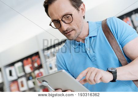 This could be a perfect gift. Male shopper focusing on a tablet and trying its technical capabilities while shopping for a new gadget at store.