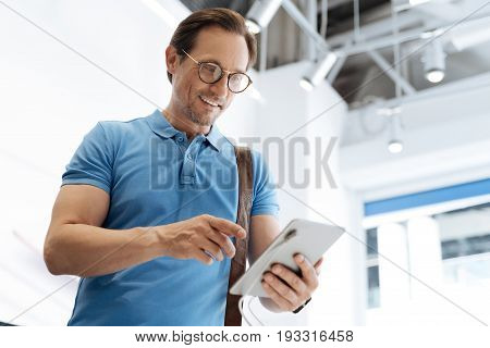 How perfect is this device. Handsome male shopper smiling cheerfully and holding a tablet while looking for a new gadget at a local store.