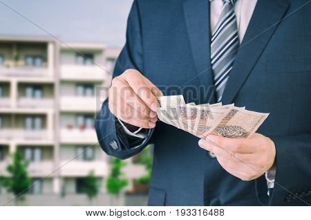 Home loan or investment in an apartment. Real estate agent holds Polish money