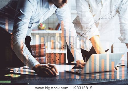 Two young businessmen using laptop at workplace with abstract business graphs. Teamwork concept. Double exposure