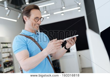 So amazed. Radiant male of business standing at a display while holding a keyboard and regarding it with curiosity at shop.