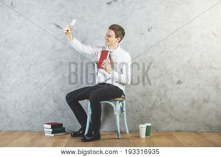 Young european taking selfie with book in interior with coffee cups and other items on wooden floor. Concrete wall background. Social media concept