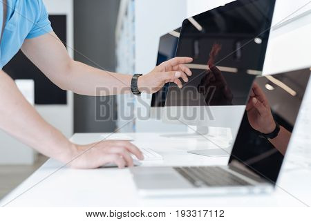 It looks amazing. Shot of a male customer using a mockup personal computer while choosing a new gadget and shopping at a department store.