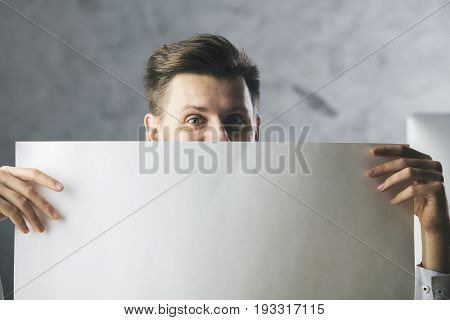 Happy businessman covering face with large empty paper sheet. Mock up