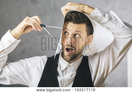 Crazy architect measuring his head with a compass on concrete background