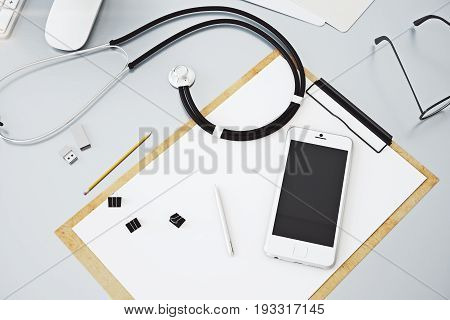 Top view of grey doctor's workplace with empty cellphone paperwork stethoscope and other items. Mock up 3D Rendering