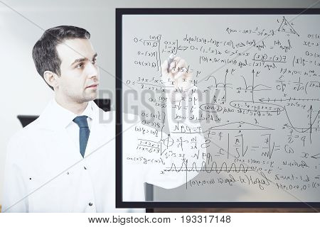 Handsome male doctor writing mathematical formulas on glass board. Science concept