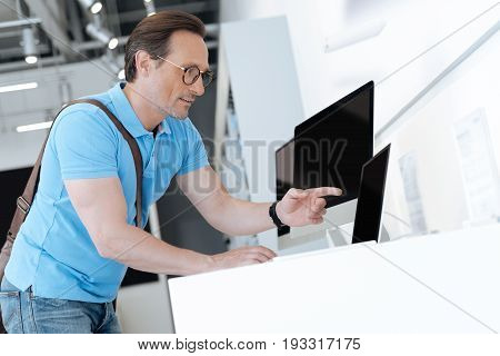 Wait what is that. Adult shopper wearing casual attire leaning on a display and pointing his finger at a template laptop while walking around an electronics shop.