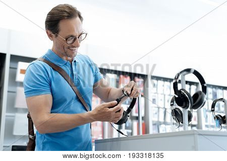 These are of high quality. Adult male customer standing at a store display while shopping for new headphones at a local department store.