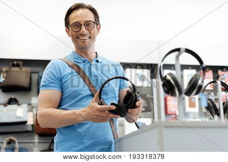 I want to buy them. Shot of a radiant male shopper holding a pair of black headphones while standing at a store display and shopping at an electronics store.