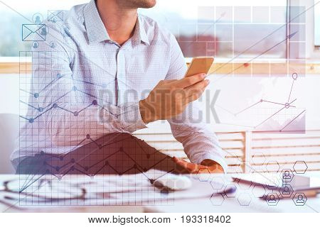 Young businessman using cellphone in modern office with digital business charts. Analysis concept. Double exposure