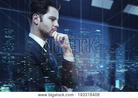 Side portrait of handsome young businessman in office on creative night city background. Executive concept. Double exposure