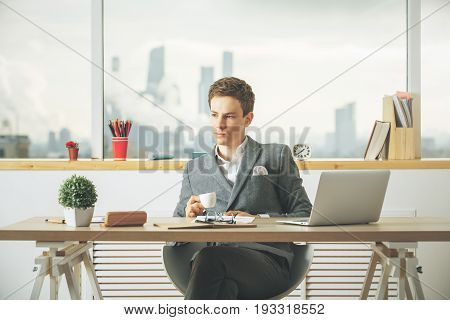 Attractive caucasian guy drinking coffee and using laptop in modern office with blurry city view and items on desktop