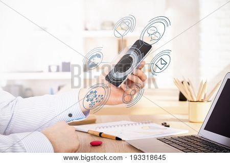Businessman using smartphone with menu hologram while sitting at desktop with laptop and supplies. Blurry background. Technology concept