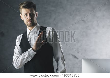 Young businessman saying no with hand on concrete background