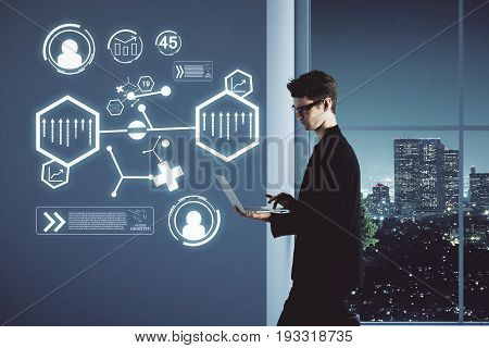 Side view of handsome young businessman standing in interior with night city view and using laptop with abstract business projection. Future concept. 3D Rendering