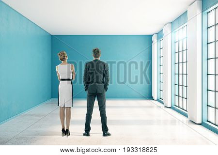 Back view of thoughtful young businessman in woman in unfurnished blue interior with city view and sunlight. Teamwork concept. 3D Rendering