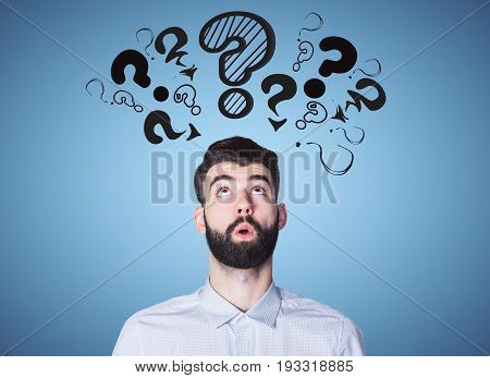 Surprised young man on blue background with drawn question marks. Ask concept