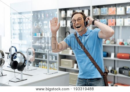 The song of my childhood. Waist up shot of an extremely excited man testing out the latest model of headphones while shopping for a pair of loudspeaker drivers at a department store.