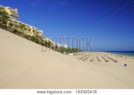 View on the beach Playa de Morro Jable with sand dune palm trees resorts and beautiful water colors of the ocean. Morro Jable the Canary Island Fuerteventura Spain.