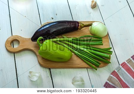 Eggplant sweet pepper and green onion on a cutting board. Cooking. Ingredients for saute. Side view.
