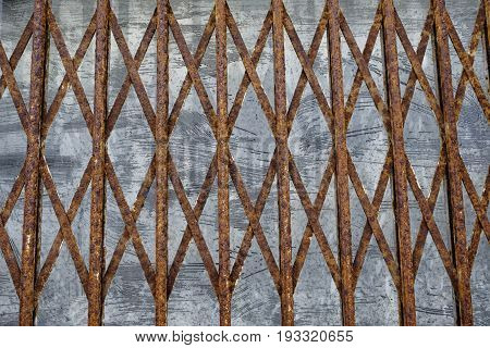 Grungy rusty iron trellis against a textured gray metal background