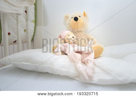 Two teddy bears in baby cott sitting on white pillow. Crib lovingly prepared by mother for the baby to be born
